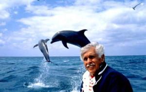 Легендата във фрийдайвинга Жак Майол, сниман в морето на фона на скачащи над водата делфини. На снимката долу целува любимия делфин Клоун.